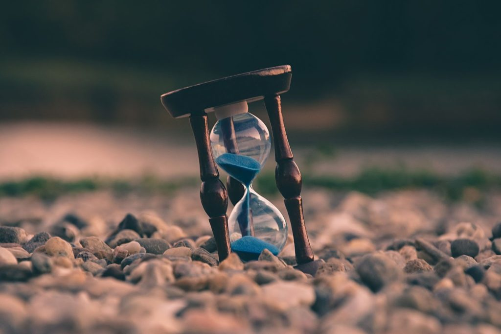 an image of hour glass timer which implies -Ways to Stop Procrastinating!